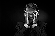 Mature man in full suit with headache, close up - MAE005689