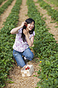 Germany, Bavaria, Young Japanese woman picking strawberries in field - FLF000204