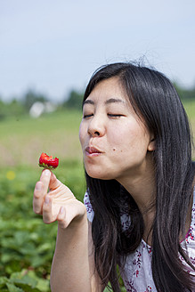 Germany, Bavaria, Young Japanese woman eating strawberry in field - FLF000215