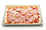 Pizza topped with salami, cheese and peppers on baking tray, close up - MAEF005672