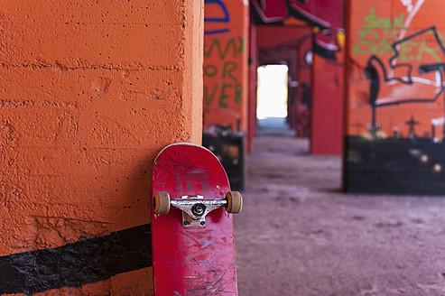 Germany, North Rhine Westphalia, Duisburg, Skateboard against graffiti sprayed wall - KJF000185