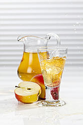 Glass of apple juice besides apples and pitcher - CSF016396