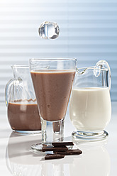 Ice cube falling into Glass of chocolate milk with carafes and pieces of chocolate besides - CSF016430
