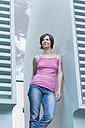 Germany, North Rhine Westphalia, Bonn, Woman leaning at building, smiling - KJF000196