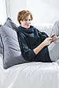 Young woman using mobile on couch, portrait - MAEF005749