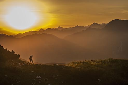 Austria, Salzburg Country, Man hiking through Niedere Tauern mountains at sunrise - HHF004307