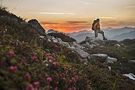 Austria, Salzburg Country, Man hiking through Niedere Tauern mountains at sunrise - HHF004309