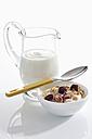 Bowl of muesli yogurt with cranberries beside yogurt carafe on white background, close up - CSF016566
