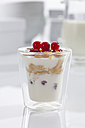 Glass of yogurt with muesli, cornflakes and red currants on white background, close up - CSF016584