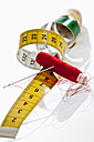 Needle, thread and measure tape on white background, close up - CSF016614