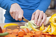 Germany, Bavaria, Munich, Young woman chopping vegetables in kitchen, close up - RBF001100