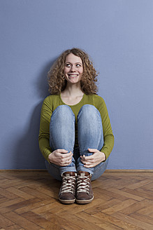 Germany, Bavaria, Munich, Young woman sitting on floor, smiling - RBF001150