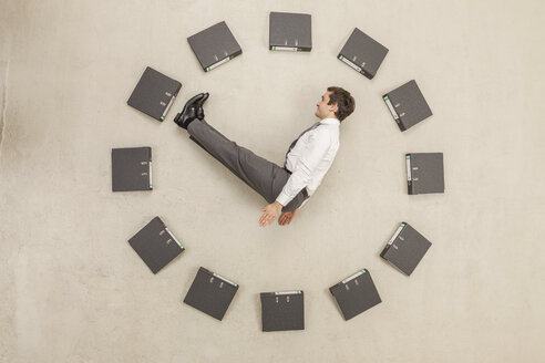 Businessman inside circle of files forming clock - BAEF000465