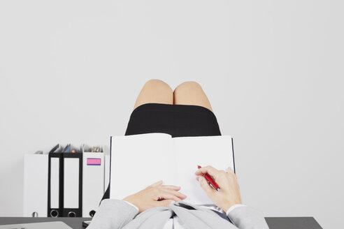 Businesswoman lying on desk with empty folder - GWF002701