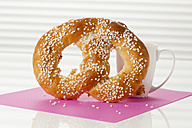 Sweet pretzel with cup of coffee, close up - CSF016819