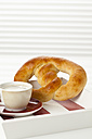 Sweet pretzel with cup of coffee, close up - CSF016822