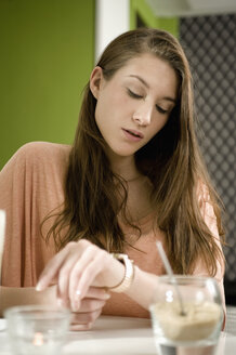 Germany, Bavaria, Munich, Young woman sitting at table in cafe, checking time - RNF001102
