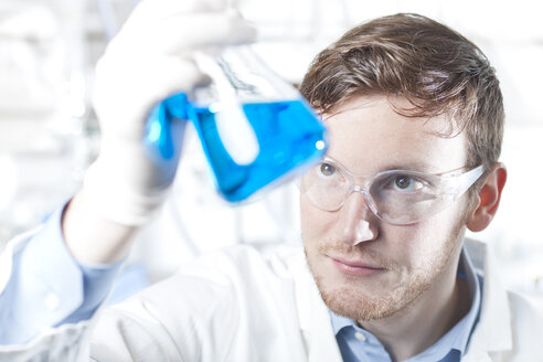 Germany, Young scientist checking blue liquid in erlenmeyer flask - FLF000231