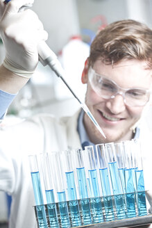 Germany, Young scientist pipetting blue liquid into test tubes, close up - FLF000269