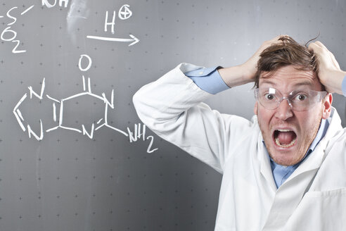 Germany, Young scientist with angry facial expression and chemical equation on chalk board - FLF000299