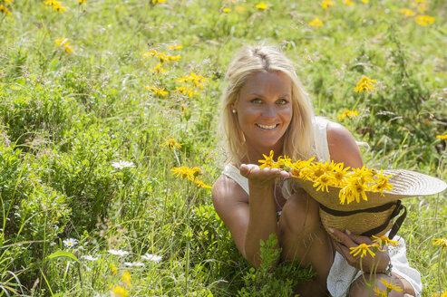 Austria, Altenmarkt-Zauchensee, Mid adult woman in alpine meadow with arnica - HHF004483