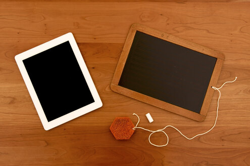 Old chalk board with digital tablet on wooden table - JEDF000009