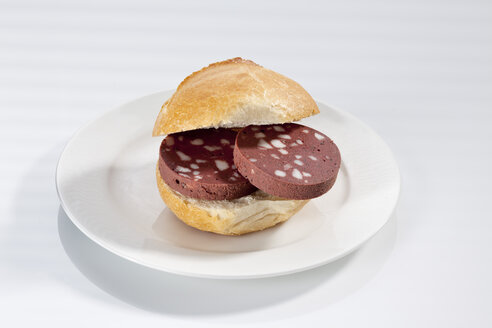 Sandwich of bread roll with black pudding on plate, close up - CSF017243