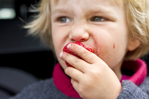 Girl eating strawberry, close up - JFEF000007