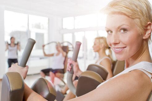 Germany, Brandenburg, Women exercising in gym, smiling - FKF000122