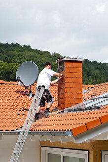 Europe, Germany, Rhineland Palatinate, Man covering chimney with roofing shingles - CSF017670