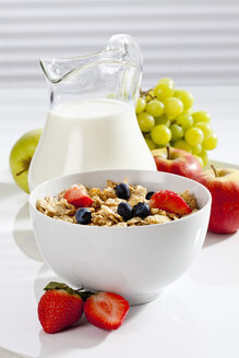 Bowl of cornflakes with various fruits and milk, close up - CSF017627
