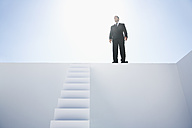 Businessman in black suit standing on wall - PDYF000375