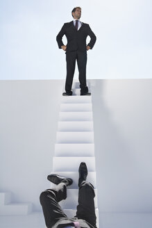 Businessman standing on stairs and other one falling down - PDYF000387