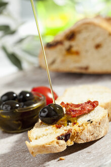 Pouring olive oil on slice of bread with olive and dried tomato, close up - CSF017747