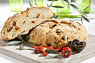 Loaf of bread with olive and tomato, close up - CSF017750