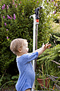 Germany, Girl in garden playing with water from lawn sprinkler - JFE000063