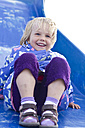 Germany, Girl playing on blue slide, smiling - JFE000067