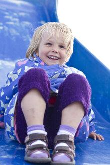 Germany, Girl playing on blue slide, smiling - JFE000067