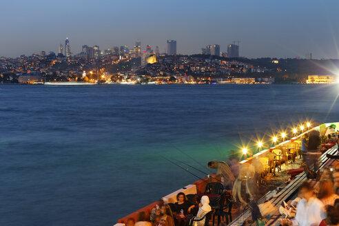Turkey, Istanbul, People sitting in cafe at Bosphorus, Beyoglu and Sisli in background - SIE003499