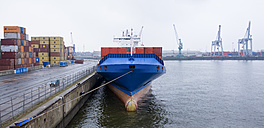Germany, Hamburg, Blue container ship docked on pier and crane in background - DIS000054