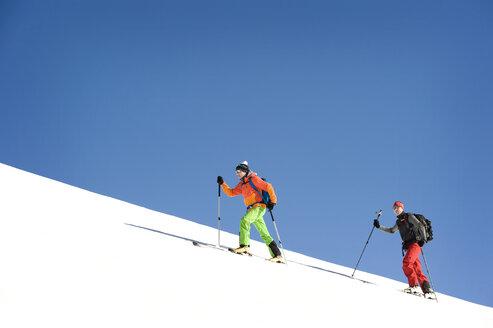Austria, Men skiing on mountain at Salzburger Land - RN001186