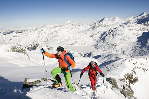 Austria, Men skiing on mountain at Salzburger Land - RN001179