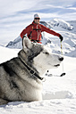 Austria, Man skiing with Avalanche Dog in snow - RN001183
