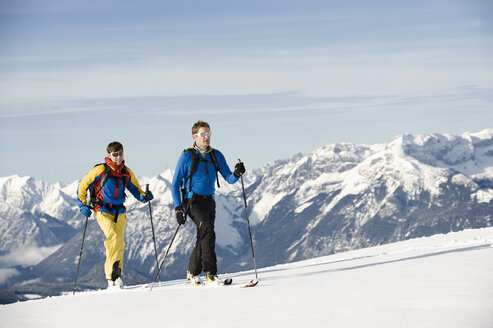 Austria, Men skiing on mountain at Alpbachtal - RN001161