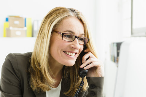 Germany, Bussinesswoman talking on telephone and using computer, smiling - SPO000119