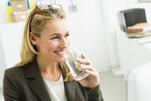 Germany, Bussinesswoman drinking water, smiling - SPO000120