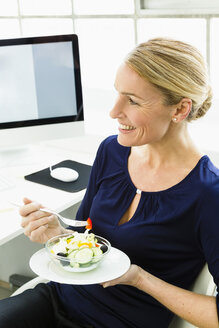 Germany, Businesswoman eating salad, smiling - SPO000171