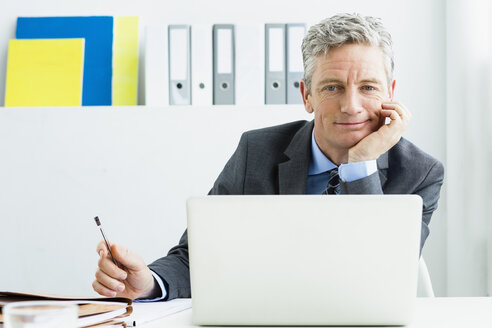 Germany, Businessman using laptop in office, smiling - SPO000178