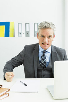 Germany, Portrait of businessman clenching teeth - SPO000193