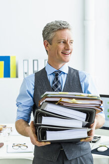 Germany, Businessman holding stack of files, smiling - SPO000210